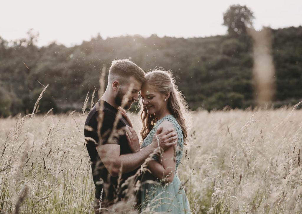 Paar steht in einer hohen Wiese. Sie legt die Hände auf seiner Brust ab, er hat seine Hände auf ihren Schultern. Beide lachen und lehnen die Stirn aneinander